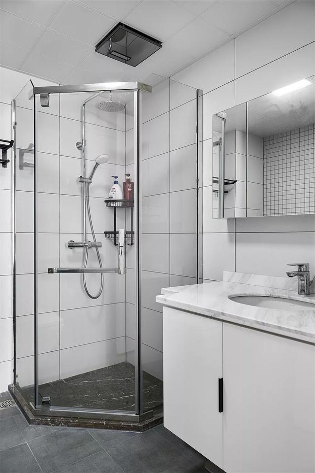 白色的浴室柜和大理石台面,淋浴区以棕色砖区分开来,整个主卫空间